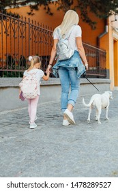 Back to school. Love of mother and daughter. Young mom and her  daughter walking with dog. Mothers day.