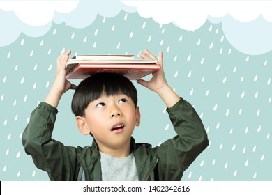 'Back to school' A lovely little boy holds his lesson books to cover his head from rain drops. Monsoon, Education, Intelligence, Kids Exploring, Child development, Emotional Quotient, EQ-IQ concept.