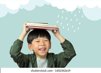 'Back to school' A lovely little boy holds his lesson books to cover his head from rain drops. Monsoon, Education, Kids Exploring, Intelligence, Child development, Emotional Quotient, EQ-IQ concept.