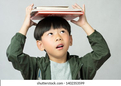 'Back to school' A lovely little boy having fun holding his lesson books on his head. Education, Smart kids, Child development, Genius, Kids Intelligent, High IQ, Emotional Quotient, IQ-EQ concept.