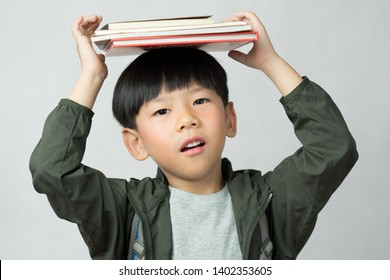 'Back to school' A lovely little boy having fun holding his lesson books on his head. Education, Smart kids, Child development, Genius, Kids Intelligence, High IQ, Emotional Quotient, IQ-EQ concept.