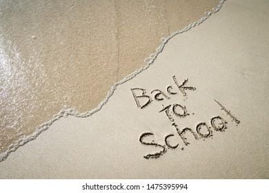 Back to School message handwritten on smooth sand beach with incoming wave