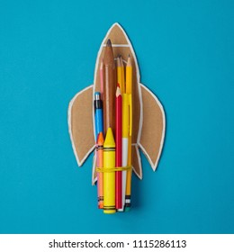Back to school minimal concept with rocket and pencils. View from above