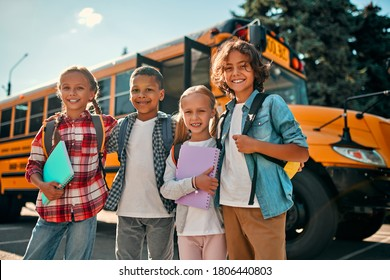 Back to school. Multiracial pupils of primary school near school bus. Happy children ready to study.