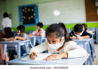 Back to school. New normal children are wearing facemasks sitting at desks in class room