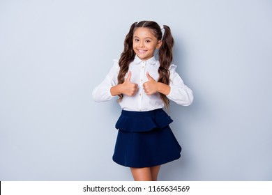 Back to school. Nice cute sweet tender cheerful positive small little girl with curly pony-tails in white formal shirt and blue skirt, showing two thumbs-up. Isolated over grey background