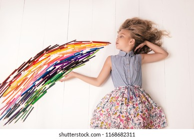 Back to school. A nice young girl in a dress with butterflies lies on the floor and blows a stream of colored pencils