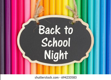 Back to School Night text on a chalkboard with colorful pencil crayons