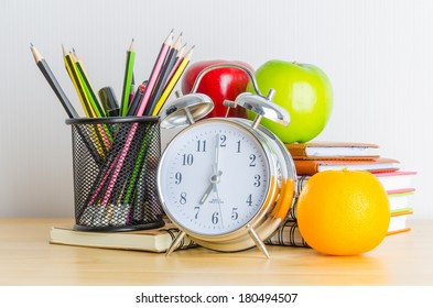 Back to school , note book , clock , pencil , apple on wood table