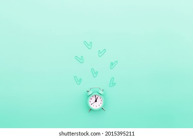 Back to school, office work conceptual flat lay with alarm clock, clips and copy space area for text. Concept of time to work, be in time and wake up early idea. Turquoise background and alarmclock