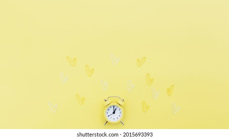 Back to school, office work conceptual flat lay with alarm clock, clips and copy space area for text. Concept of time to work, be in time and wake up early idea. Yellow background and alarmclock