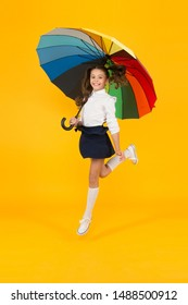 Back to school on September 1. Adorable schoolgirl with rainbow umbrella on September 1 on yellow background. Small child going to school on September 1. Little girl at first school day, September 1.