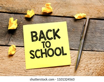 Back to school. Paper card with text back to school on wooden background