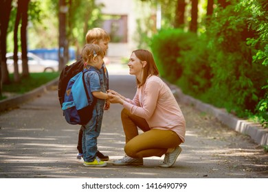 Back to school. Parent taking child to school. Pupil of primary school go study with backpack. Mom and daughter and son go hand in hand. Beginning of lessons.  First day of fall. Elementary student.