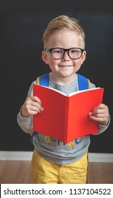 Back to school. Pupil of primary school  with a book in class room with blackboard on a background. Happy smiling kid go to elementary school.