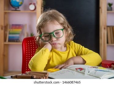 Back to school. Pupil sleeping in class.  Tired little child girl doing homework with head in hands. Hard tusk of reading and writing for elementary school. Boring test in class room.