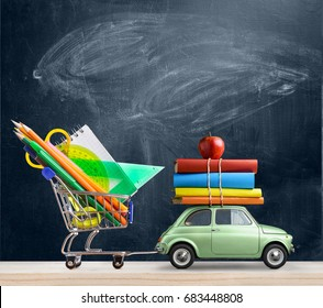 Back to school sale background. Car delivering shopping cart with accessories, books and apple against blackboard.