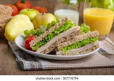 Back to school sandwich, simple sandwich whole grain bread, salad, ham and cheese. Milk and fresh juice, fruit for bio healthy