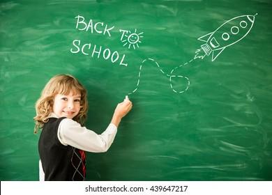 Back to school. Schoolchild in class. Happy kid against green blackboard. Child writing on chalkboard. School kid in classroom. Education and creativity concept