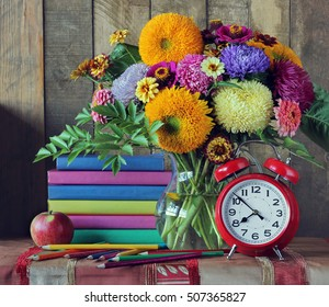 Back to school. September 1, knowledge Day, teacher's Day. Still life with books, bouquet, and alarm clock.