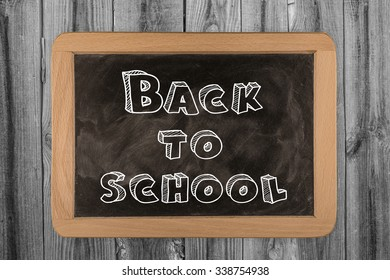 Back to school Sign on blackboard on wooden background