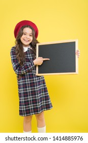 Back to school. Small school child pointing finger at blank blackboard on yellow background. Cute little schoolgirl with chalkboard on school day. Adorable pupil having school lesson, copy space.