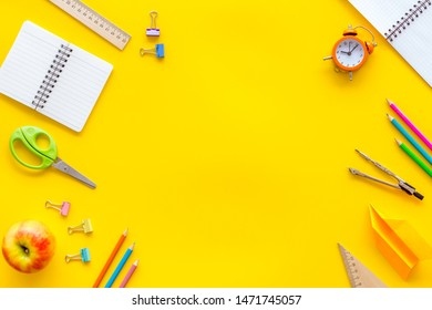 Back to school with stationary, apple, notebook and alarm clock on yellow student desk background top view mock-up