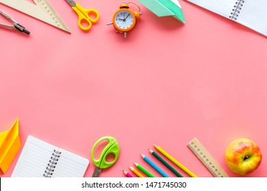 Back to school with stationary, notebook and alarm clock on pink student desk background top view mockup