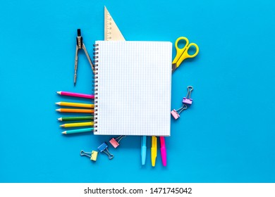 Back to school with stationary, notebook and scissors on blue student desk background top view mockup
