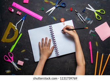 Back to School: Stationery and children's hands on a dark table.