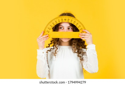 Back to school. Student learning geometry yellow background. Measure angles in degrees. School lessons. Adorable cute pupil. She loves studying. Small girl holding protractor for geometry lesson.