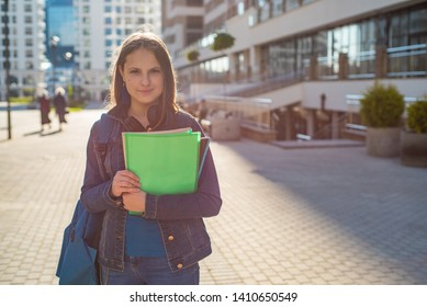 Back to school student teenager girl holding books and note books wearing backpack. Outdoor portrait of young teenager brunette girl with long hair. girl on city