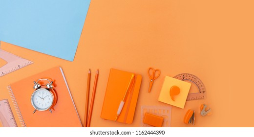 Back to school styled flat lay scene with school supplies on blue and orange background