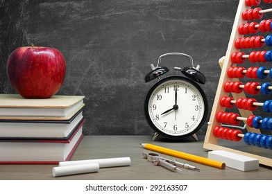 Back To School / School Supplies, an Apple and an Alarm Clock on a Desk in front of a Blackboard