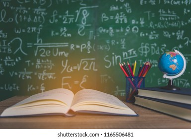 Back to school supplies. Books and blackboard on wooden background.