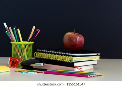 Back to school supplies. Books and red apple on chalkboard background. Still life with pencils. Copy space.