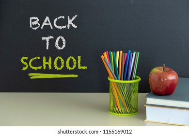 Back to school supplies. Books and red apple on dark background. Still life. Copy space.