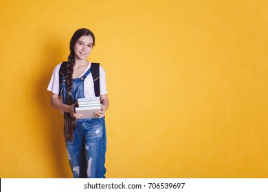 Back to school. Teen girl with books on a bright orange and yellow background. Place for your text.