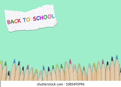 Back to school title word design with colorful text and drawing by colour pencil on scarp of paper in pastel green background.Education,Business office and Arts Concept.Copy space empty blank for text