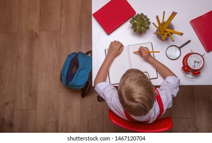 Back to school. Top view of child sitting on desk with book, bag, pencil, while doing homework. Student writing in an empty notebook. Space for text