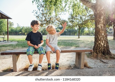 Back to school: Two boys resting on bench after school.