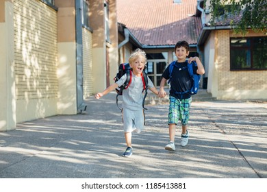 Back to school: Two happy boys with backpacks leaving school on sunny day