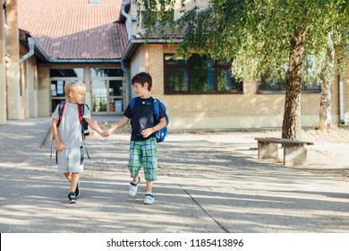 Back to school: Two happy boys with backpacks walking holding hands