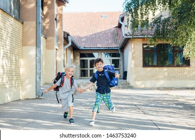 Back to school: Two happy boys with backpacks running holding hands