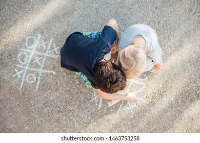 Back to school: Two happy boys drawing with chalk on asphalt