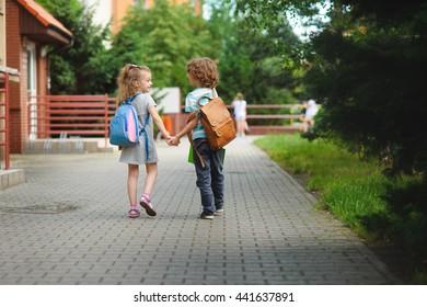 Zurück zur Schule. Zwei junge Schüler gehen Hand in Hand zur Schule. Sie sprechen über etwas, das knauserig ist. Hinter dem Rücken eines jeden sitzt.  Kleine erste Grader. Schulkinder.