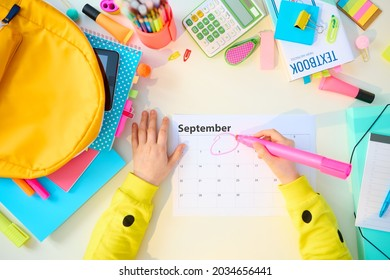 Back to school. Upper view of modern child with workbooks, stationary, textbook, september calendar and backpack at white table at home.