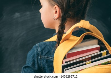 Back to school. Back view of young girl with open backpack fully stuffed with books.