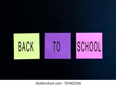 Back to school words on sticky paper, black background
