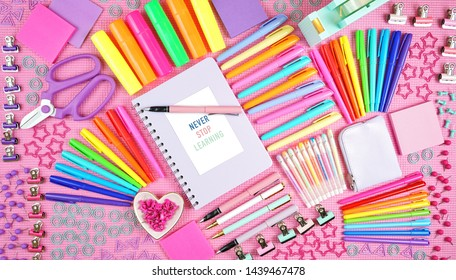 Back to school or workspace colorful stationery overhead on pink background flat lay.